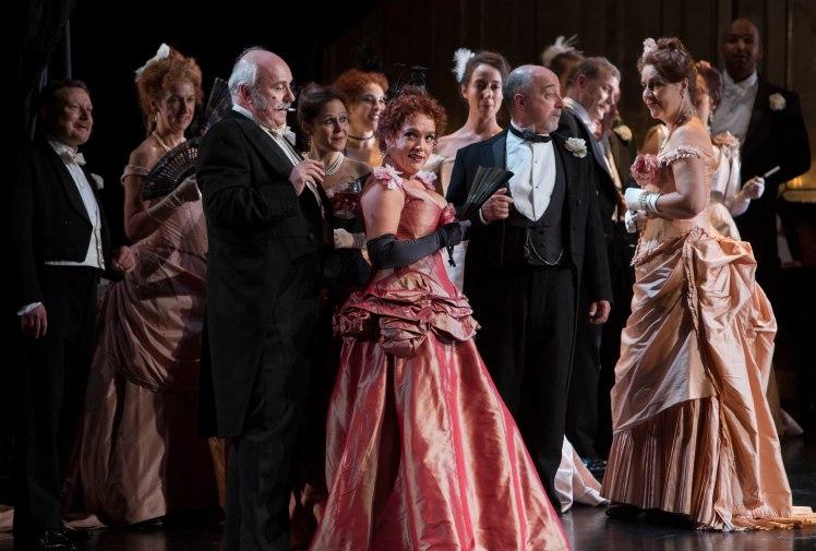 WNO La traviata - Philip Lloyd-Evans (Marquis d'Obginy), Rebecca Afonwy-Jones (Flora) and WNO Chorus. Photo credit Betina Skovbro - 3598a